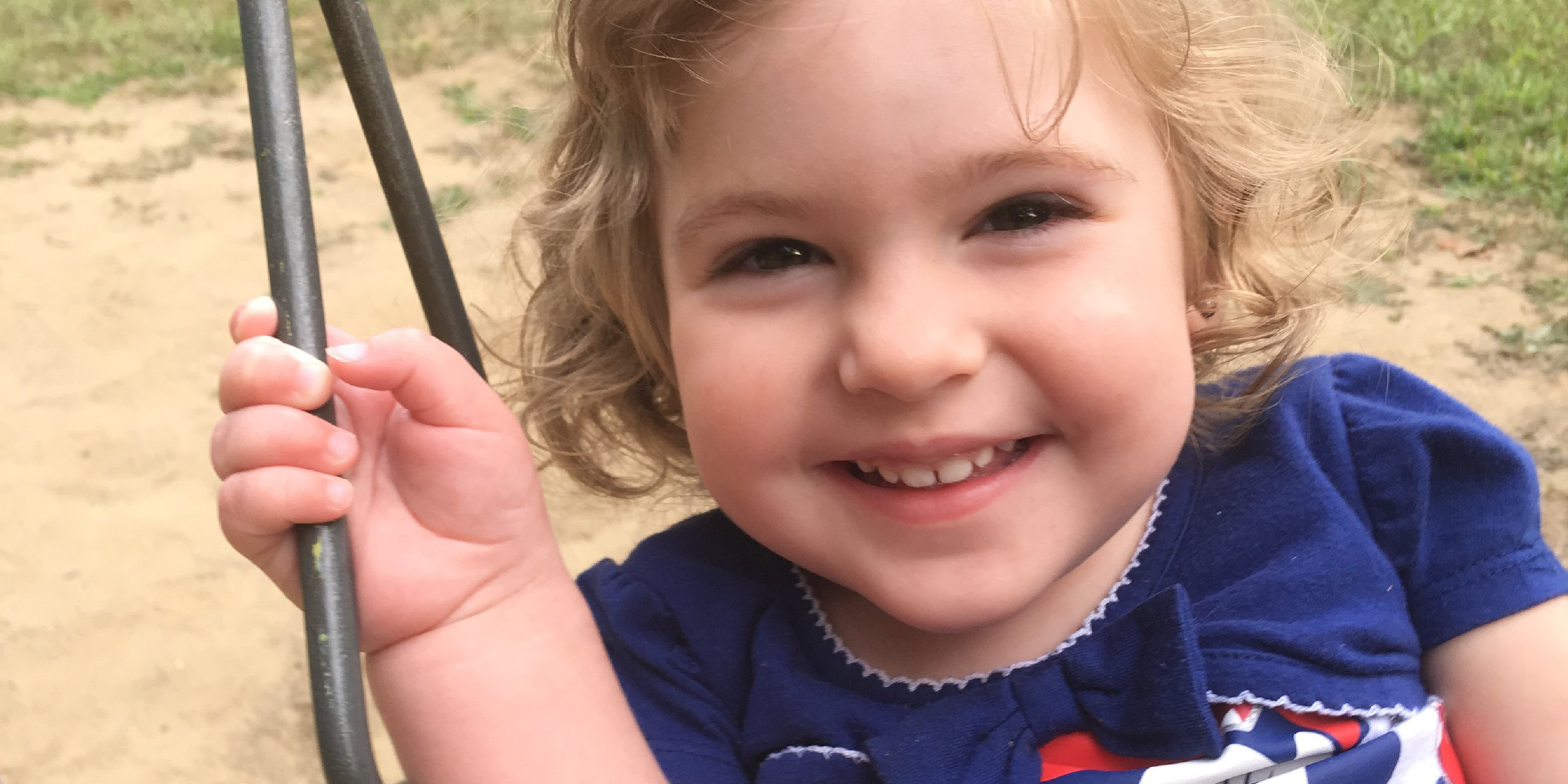 Young girl with Rett Syndrome swinging outside